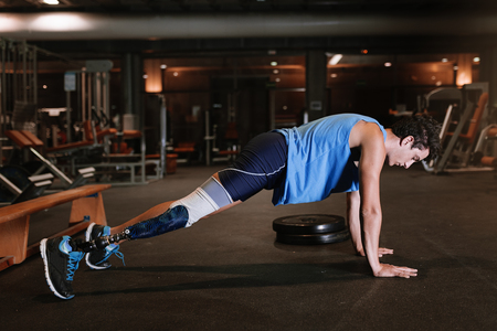 Disabled young man training in the gym. Disabled sportsman Concept. Stock fotó