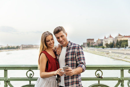 Portrait of young couple using mobile phone in the street. Mobile Concept. Stock Photo