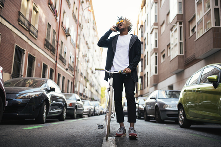 Handsome young man using mobile phone and fixed gear bicycle in the street.