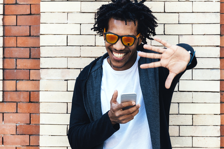 Portrait of afro handsome man using his mobile in the street. Imagens