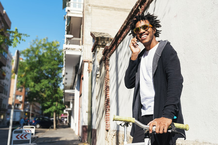 Afro young man using mobile phone and fixed gear bicycle in the street.
