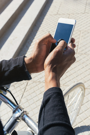 Close up of young man using mobile phone and fixed gear bicycle in the street.