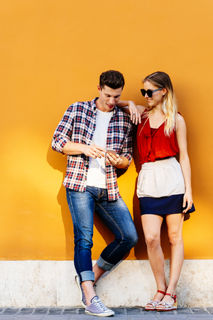 Portrait of young couple using mobile phone in the street. Mobile Concept. Standard-Bild