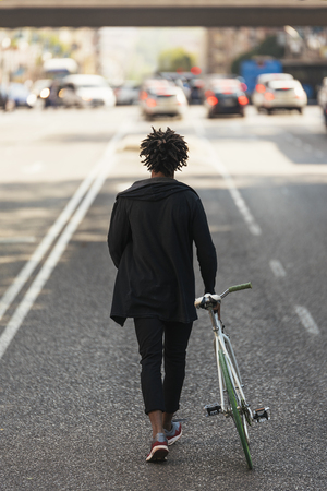 Handsome afro man walking with his bike in the street. Standard-Bild