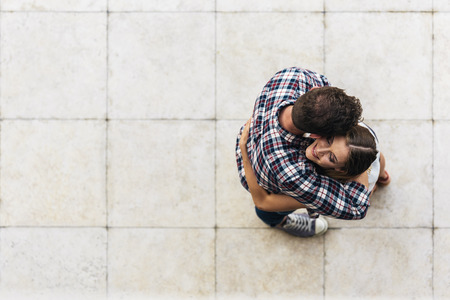 Young loving couple hugging in the street. From top view. Young Love Concept.