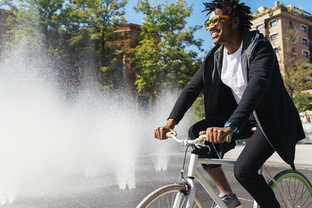 Handsome afro man riding a bike in the street.