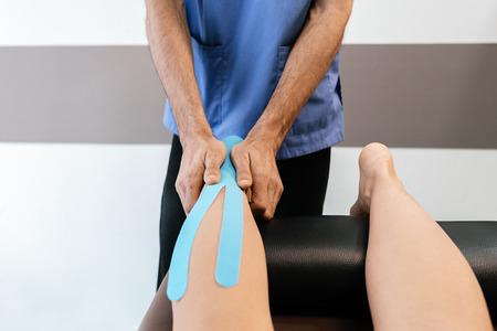 Fisioterapeuta dando terapia de terneros a una mujer en la clínica. Concepto de tratamiento físico