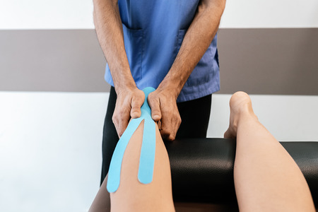 Physiotherapist giving calf therapy to a woman in clinic. Physical treatment concept