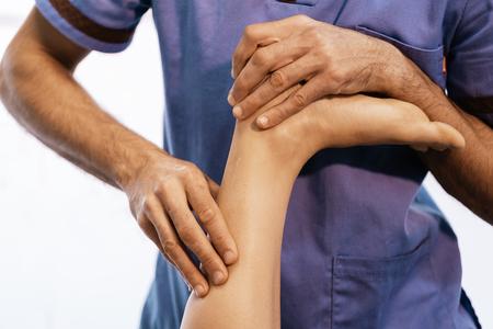 Fisioterapeuta dando terapia de rodilla a una mujer en la clínica. Concepto de tratamiento físico