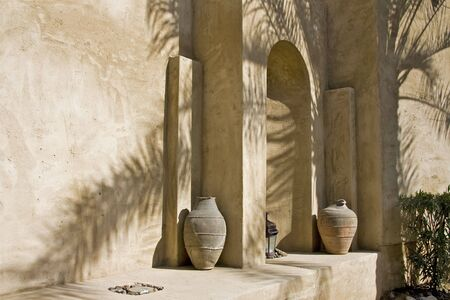 stoneworks: Arabian arch in shadow of palm tree with old arabic pottery Stock Photo