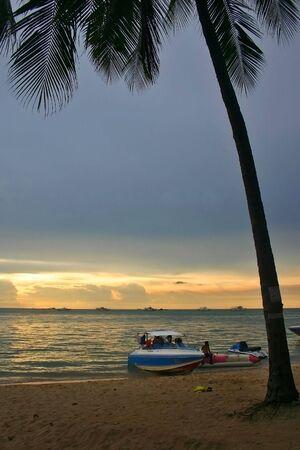 Pattaya Beach Sunset showing Palm Tree and Speed Boat. photo