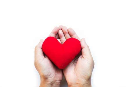red pillow heart in two palms hand, for Valentine day, happy New Year celebration, the meaning of love, warm feeling by sending the messages to someone the best wishes, and love, on white background Stock Photo
