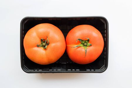 Two tomatoes in the unpack black plastic box from supermarket, healthy foods Stock Photo