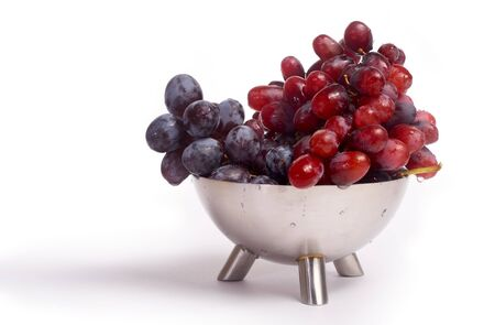 damp: Black and red damp grapes in a metal vase Stock Photo
