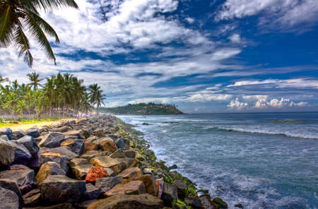 View of a rocky beach in kovalam and Leela on the hill top. photo