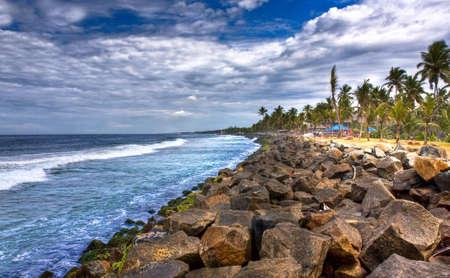 kovalam: coast line of kovalam in kerala full of rocks and coconut trees Stock Photo