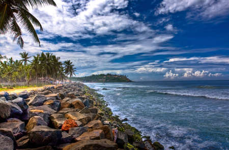 kovalam: coast line of kovalam in kerala full of rocks and coconut trees and a hilltop in the backdrop Stock Photo