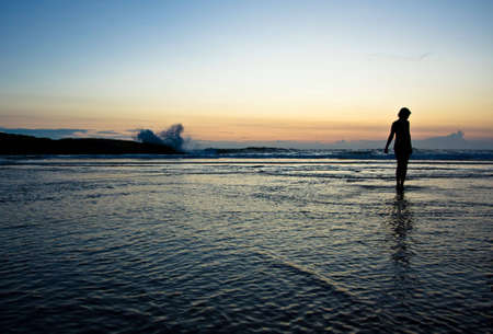 kovalam: silhouette of a girl on a beach enjoying sunset and strong waves Stock Photo