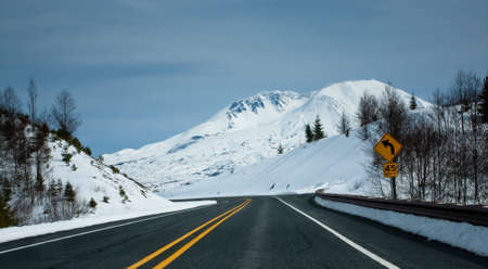 a clean road towards a snow capped mountain. Also symbolizes the path towards a peak or towards qrowth. photo