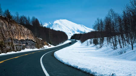 winter road: a clean road towards a snow capped mountain. Also symbolizes the path towards a peak or towards qrowth.