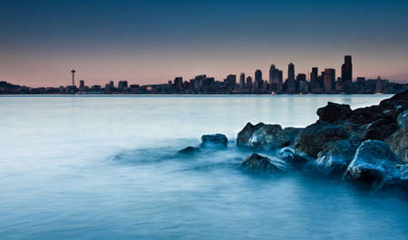 seattle: A dreamy look of a city skyline from a beach. The foreground covered with pebbles, rocks and an old tree log. Waves and water ripples provide a creamy and steamy effect with the sky scappers in the background marking the city skyline Stock Photo