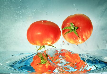 sputter: tomatoes in water on a blue background