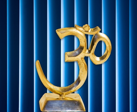 golden Om in base with dark and with glowing blue background Stock Photo - 9439799