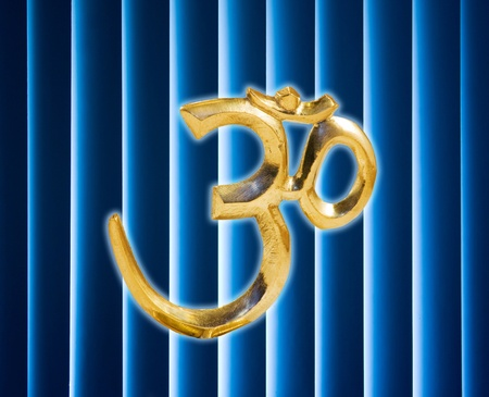 golden Om in base with dark and with glowing blue background photo