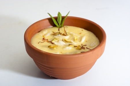 Indian sweet Firni in round earthen bowl photo