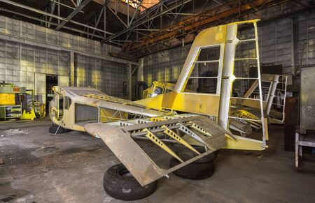 aviation: Abandoned aviation factory of small aircraft. The partially-built airplane in a dark industrial building at night.
