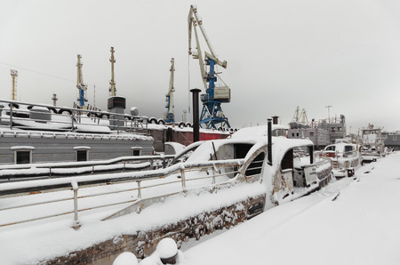 berth: Night view of harbor cranes on the waterfront of the port covered with snow. Abandoned ships moored at the berth Stock Photo