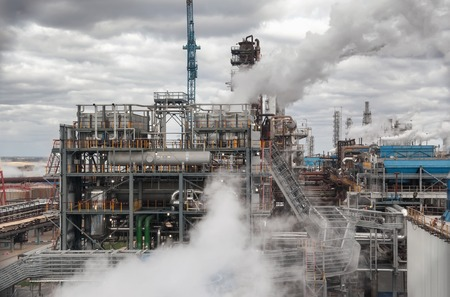 amoníaco: Fábrica de productos químicos para la producción de amoníaco y nitrógeno en la fertilización durante el día. El vapor de agua del sistema de refrigeración Foto de archivo