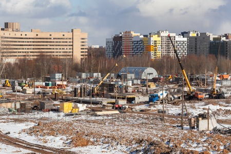 erecting: The construction site of the future apartment house in the winter against the backdrop of modern buildings. Stock Photo