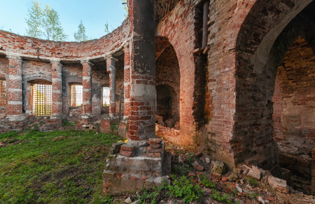 rotunda: Ancient rotunda with columns without a dome. The brick ruins of the interior of an abandoned temple overgrown with grass