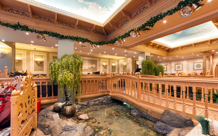 deluxe: MOSCOWRUSSIA - DECEMBER 2014. The interior of the deluxe restaurant of Uzbek cuisine - Babay Club in an oriental style. Pond and wooden bridge in the restaurant