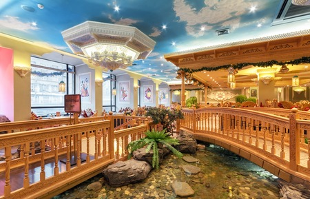 moldings: MOSCOWRUSSIA - DECEMBER 2014. The interior of the deluxe restaurant of Uzbek cuisine - Babay Club in an oriental style. Pond and wooden bridge in the restaurant
