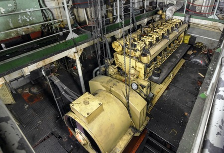 diesel generator: The ships hold with  yellow diesel engine mounted on ship. Engine room on a old cargo boat ship.