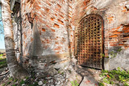 front elevation: Ancient iron door decorated with wrought-iron details. Entrance to the abandoned russian church Stock Photo