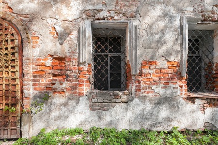 front elevation: Vintage window with iron bars on the wall of an abandoned temple