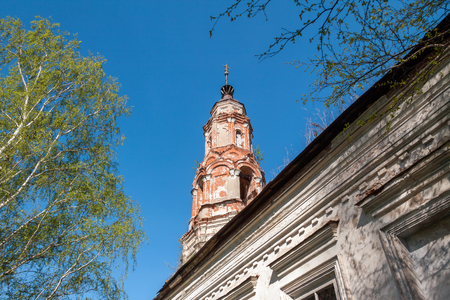 front elevation: Old abandoned brick bell tower against the blue sky