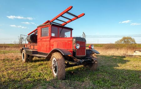 antique fire truck: Old retro fire truck with wooden case on the field Stock Photo