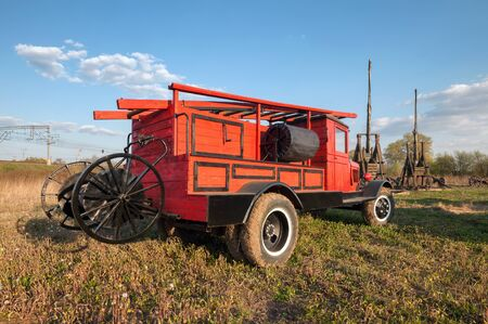 antique fire truck: Back side old retro fire truck with wooden case on the field