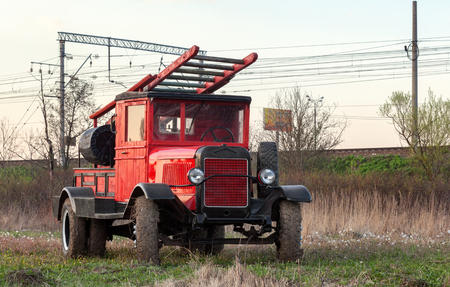antique fire truck: Front view of old retro fire truck on the field with caked mud on the wheels Stock Photo