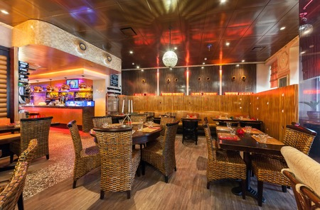 wicker bar: MOSCOW - JULY 2014: Interior of a luxury restaurantOGNI. Main room with tables, wicker furniture, wine rack, modern bar made of wood