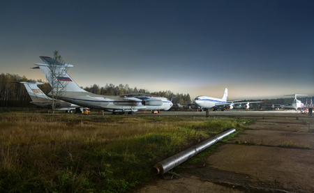 passenger aircraft: Parking older passenger aircraft at night on a background of forest and stars