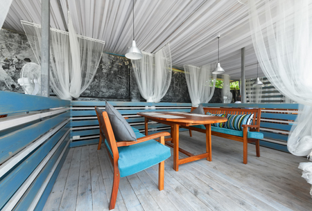 mediterranean interior: MOSCOW - JULY 2014: Interior of stylish Mediterranean cuisine Italian restaurant - SILLYCAT. Covered veranda in a nautical style. Cabin with a table and table