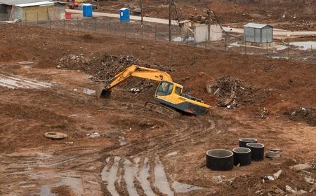 黄色の建設サイトの掘削機で泥の中で立ち往生