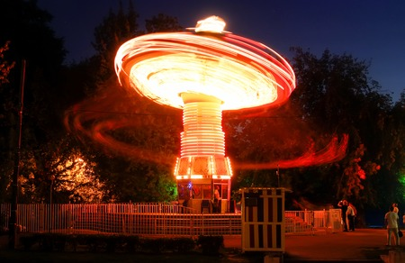 brightly: Blurred motion effect around of brightly illuminated rotating high speed carousel merry-go-round. Late in the evening in an amusement park