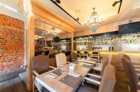 MOSCOW - AUGUST 2014: Interior elegant city restaurant RULET in loft style. Table near the mirror in the main hall with a bar