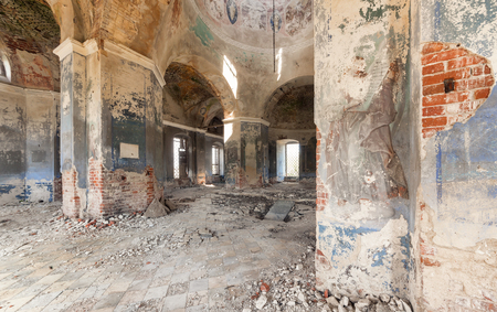 Inside an abandoned looted temple. Columns and a dome with crumbling paint and plaster Stock Photo